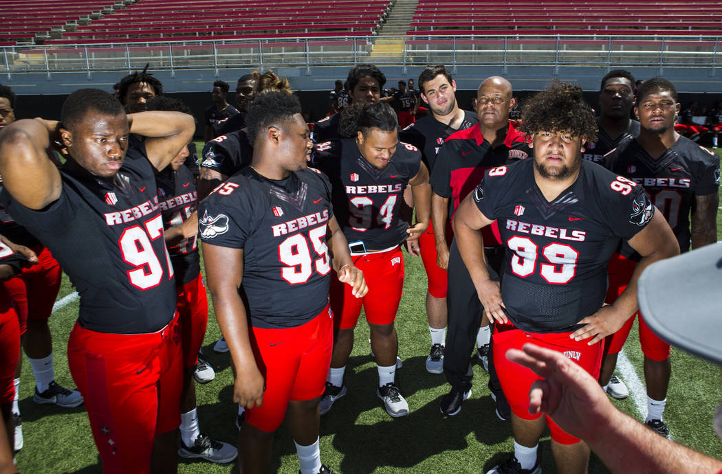 Freshman and sophomore football players including UNLV Rebels defensive linemen Jamal Holloway (97), Kolo Uasike (94), and Chris Manoa (99), gather during the team's photo day at Sam Boyd Stadium ...
