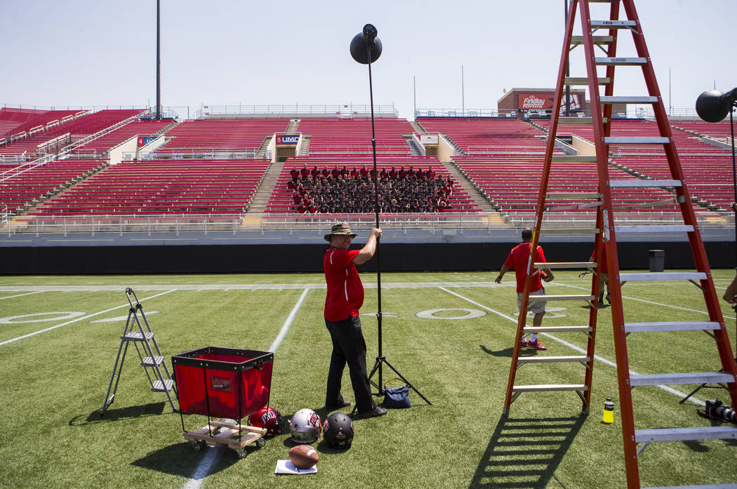 UNLV photographer Josh Hawkins, center, gets ready to take a portrait of UNLV's football team at Sam Boyd Stadium in Las Vegas on Wednesday, Aug. 8, 2018. Chase Stevens Las Vegas Review-Journal @c ...