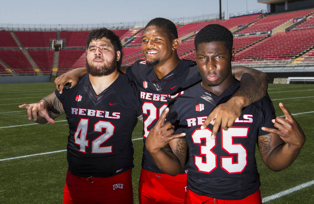 UNLV Rebels defensive lineman Salanoa-Alo Wily (42), defensive lineman Jameer Outsey (20) and running back Xzaviar Campbell (35) pose for a photo during UNLV football's photo day at Sam Boyd Stadi ...