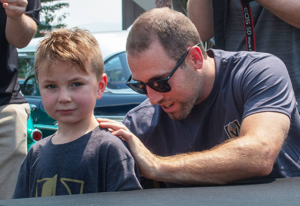 5-year-old Everett Friedlander,left, gets his T-shirt signed by one of his favorite athletes, Golden Knights defenseman Brad Hunt at a Vegas Golden Knights fan rally in Reno on Monday, Augus ...
