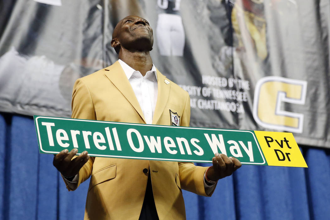 Former wide receiver Terrell Owens holds a street sign after a road was named for him following his Pro Football Hall of Fame speech, Saturday, Aug. 4, 2018, in Chattanooga, Tenn. Instead of speak ...