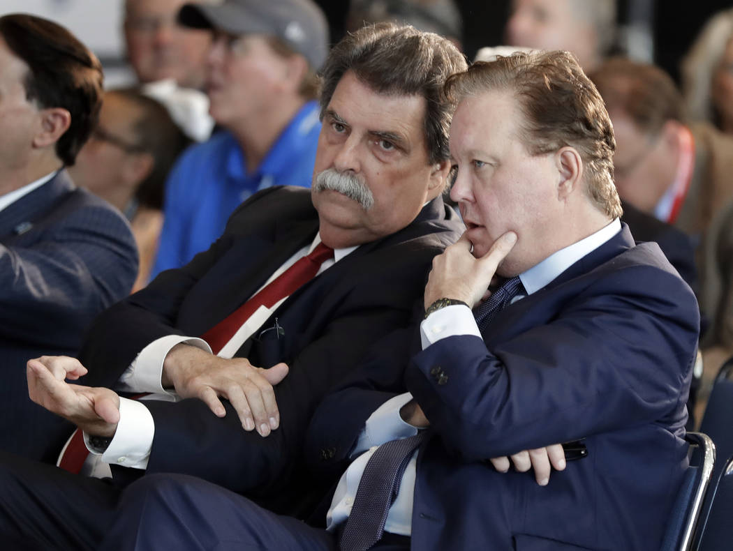 NASCAR Chairman Brian France, right, talks with Vice Chairman Mike Helton before an announcement of the 2019 class of the NASCAR Hall of Fame in Charlotte, N.C., Wednesday, May 23, 2018. (AP Photo ...