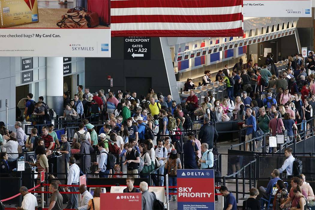 In this June 29, 2018, photo passengers wait to pass through security at Logan International Airport in Boston. As summer vacationers start to pack up and head home, Congress is considering a swee ...