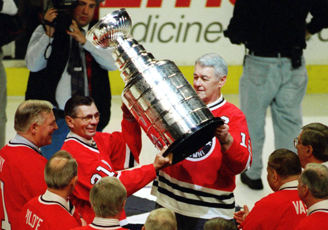In this March 17, 1996, file photo, Stan Mikita, second from left, and Ed Lizenberger hoist the Stanley Cup during ceremonies to honor the Chicago Blackhawks' 1961 Stanley Cup championship team be ...