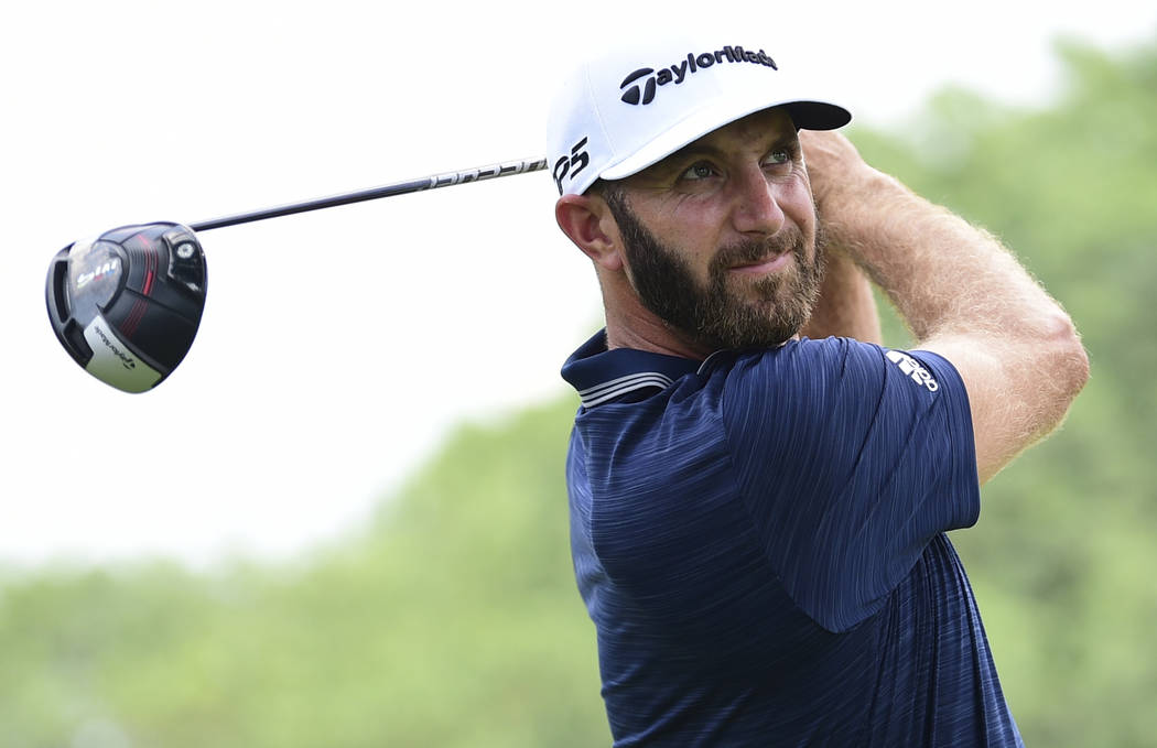 Dustin Johnson watches his tee shot on the 10th hole during the final round of the Bridgestone Invitational golf tournament at Firestone Country Club, Sunday, Aug. 5, 2018, in Akron, Ohio. (AP Pho ...