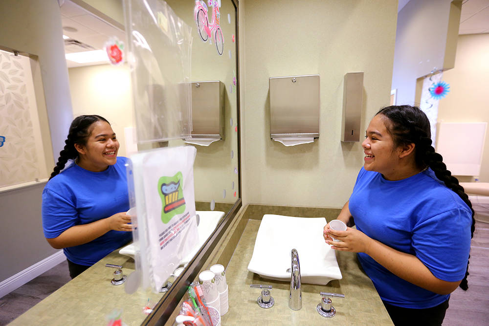 Alondra Lezama, 14, checks out her smile after Dr. Victoria Chen of Significance Orthodontics took braces off in her North Las Vegas office Tuesday, Aug. 7, 2018. Chen and her team will be donatin ...