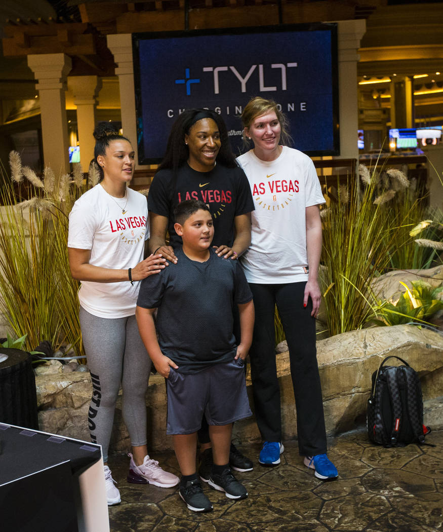 Braeden Sada, 11, poses for a photo with Las Vegas Aces players, from left, Kayla McBride, Kelsey Bone and Carolyn Swords at Mandalay Bay in Las Vegas on Saturday, July 21, 2018. Chase Stevens Las ...