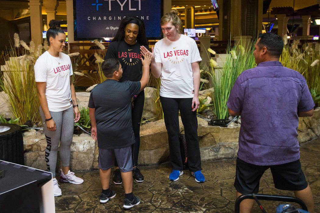 Braeden Sada, 11, high-fives Las Vegas Aces player Carolyn Swords, right, as players Kayla McBride, left, and Kelsey Bone, center, look on at Mandalay Bay in Las Vegas on Saturday, July 21, 2018. ...