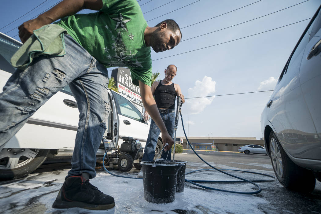 Brandon Steckler, left, and Manuel Serros, mobile car wash company owner, prepare soap at a car wash aimed at raising money to help pay funeral expenses for Brandon Steckler Jr. at The Drop in Las ...