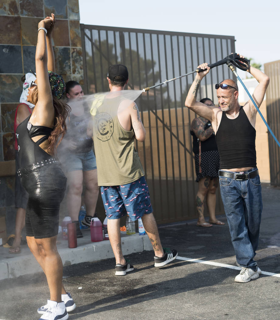 Manuel Serros, mobile car wash company owner, sprays Dayna Alvarado, sister of Brandon Steckler, at a car wash aimed at raising money to help pay funeral expenses for Brandon Steckler Jr. at The D ...