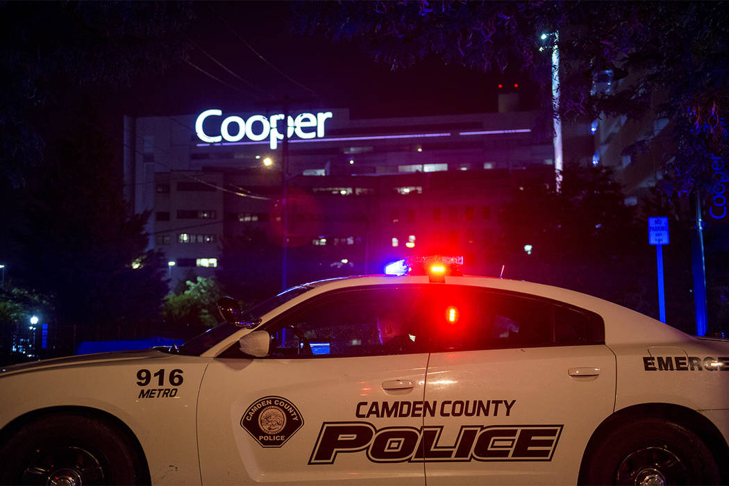 An officer is posted by Copper hospital following a shooting that left two detectives wounded in Camden, N.J., Tuesday, Aug. 7, 2018. Camden County Police Chief J. Scott Thomson said at least one ...