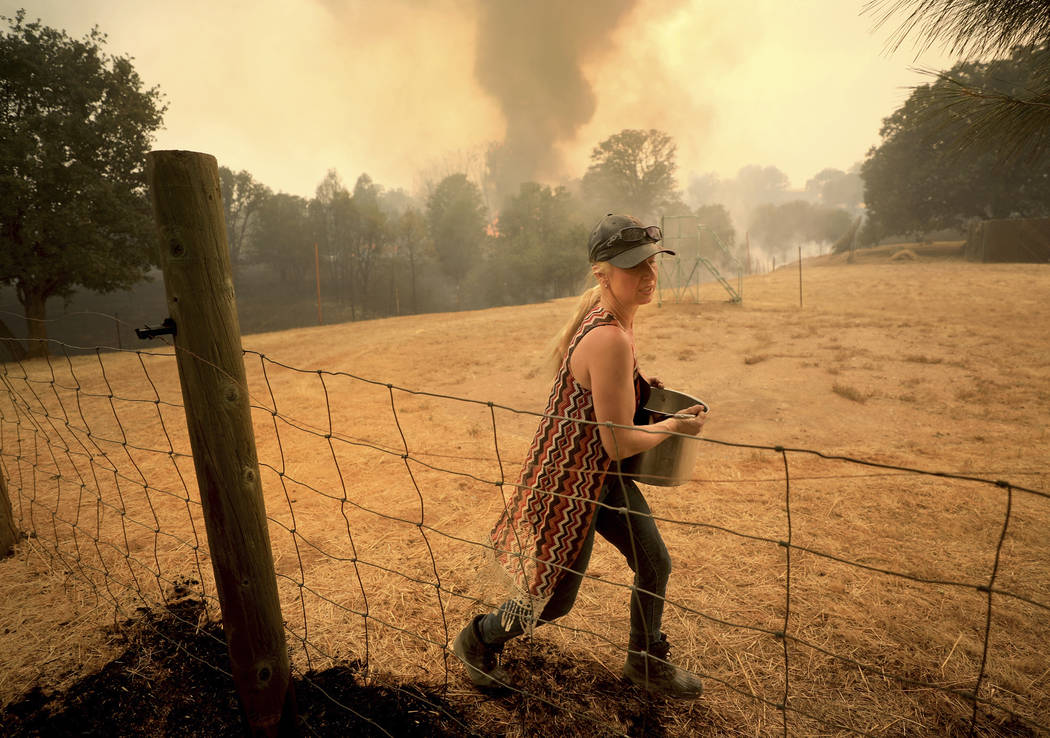 Crystal Easter uses a pot of water to put out spot fires around her home, as her neighbor's home burns to the ground in the background, Monday, Aug. 6, 2018, in Spring Valley, Calif. The Ranch Fir ...