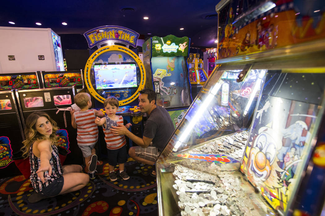 Two-year-old Henry Borrego, third from left, points to a game alongside mother Leslie Daniel with, from left, brother Emil, 4, and father Reuben Borrego, in the carnival midway at Circus Circus in ...