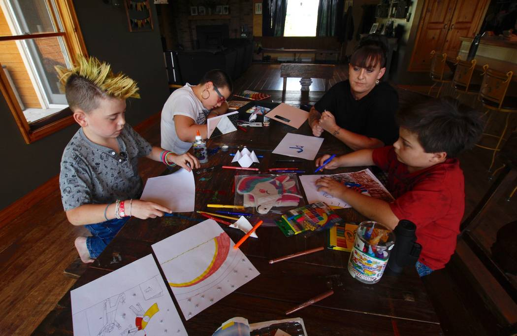 In this Aug. 1, 2018, photo, from left, Cash Miller, his sister Kaya Miller, their mother Angie Miller and their brother Jax Miller work on artwork at their kitchen table in Hartford, Wis. Angie M ...