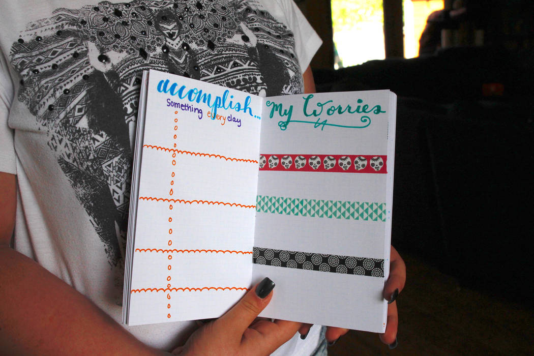 In this Aug. 1, 2018, photo, Kaya Miller holds up some of her work in a bullet journal, including use of wash tape, in Hartford, Wis. The bullet journal and wash tape are two of the hot items in t ...