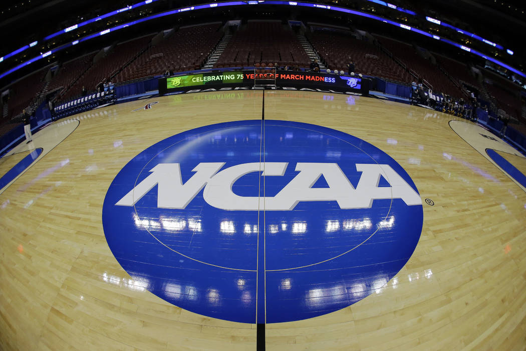 In this March 21, 2013, file photo, taken with a fisheye lens, the NCAA logo is displayed on the court during the NCAA college basketball tournament in Philadelphia. (AP Photo/Matt Slocum, File)