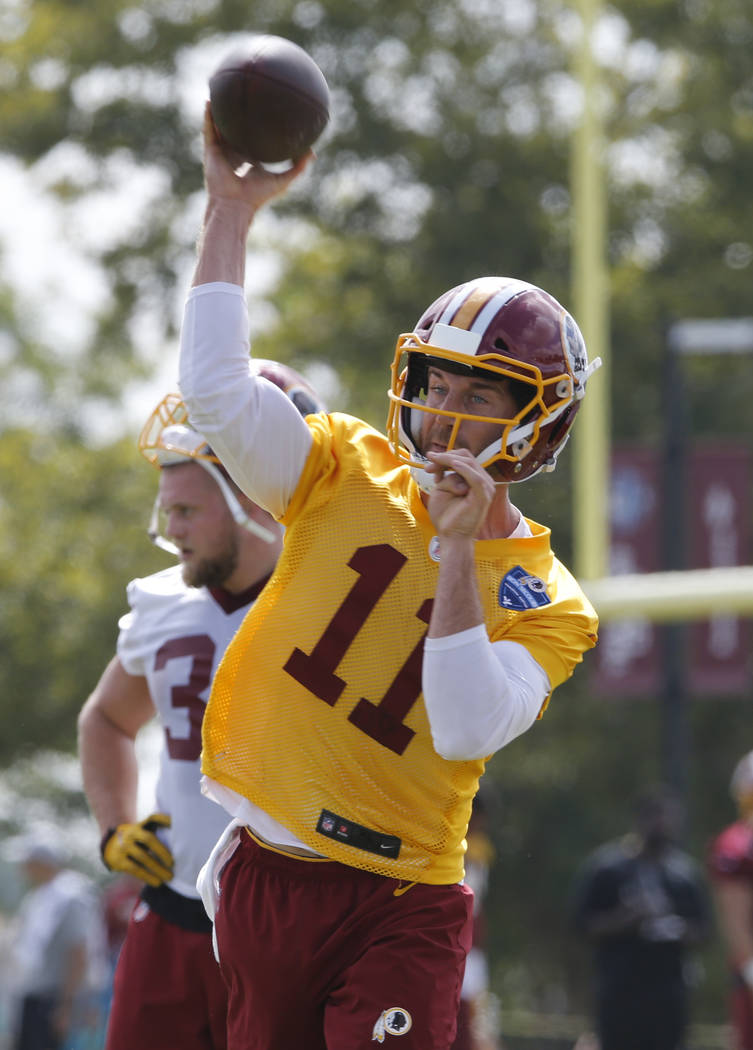 Washington Redskins quarterback Alex Smith (11) tosses a pass during drills at the start of the Redskins NFL football training camp in Richmond, Va., Thursday, July 26, 2018. (AP Photo/Steve Helber)