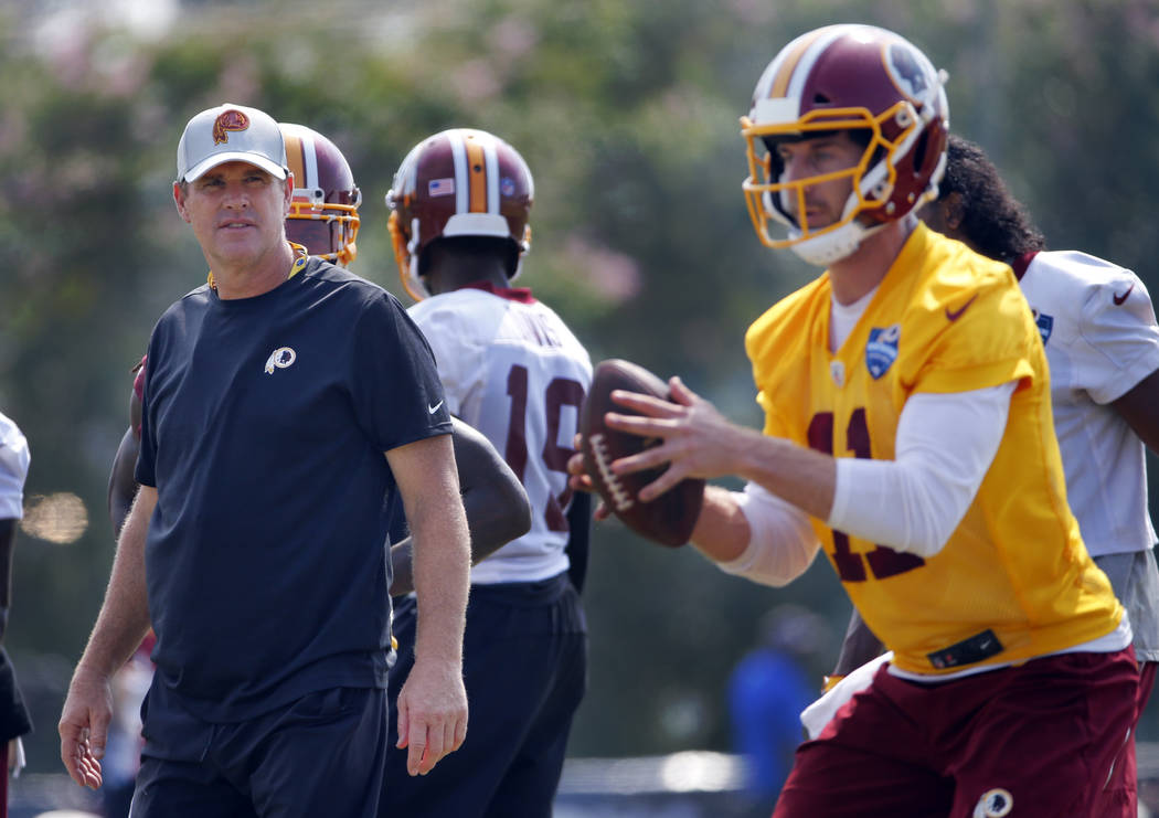 Washington Redskins head coach Jay Gruden, left, watches quarterback Alex Smith (11) during the morning session of NFL football training camp in Richmond, Va., Friday, July 27, 2018. (AP Photo/Ste ...