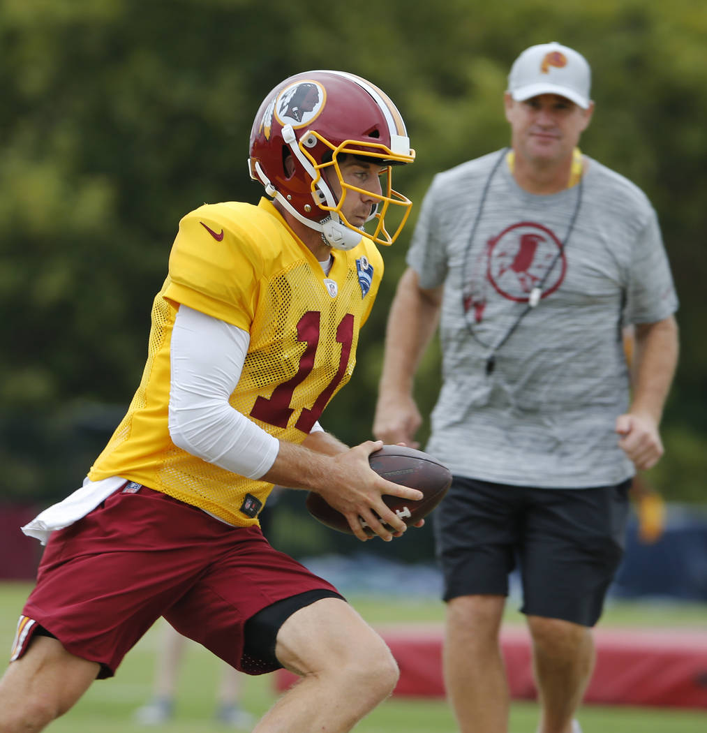 Washington Redskins quarterback Alex Smith (11) runs a drill as head coach Jay Gruden watches during the morning session of the Redskins NFL football training camp in Richmond, Va., Tuesday, July ...