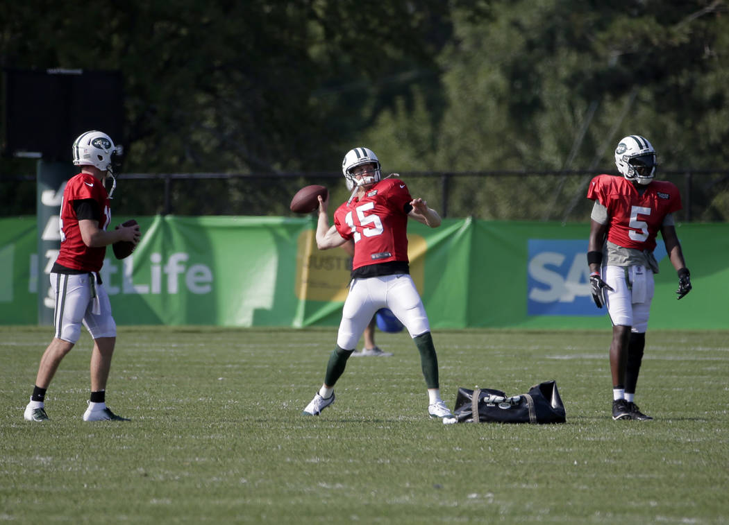 New York Jets quarterbacks Sam Darnold, left, Josh McCown, center, and Teddy Bridgewater throw footballs after a practice at the NFL football team's training camp in Florham Park, N.J., Monday, Au ...