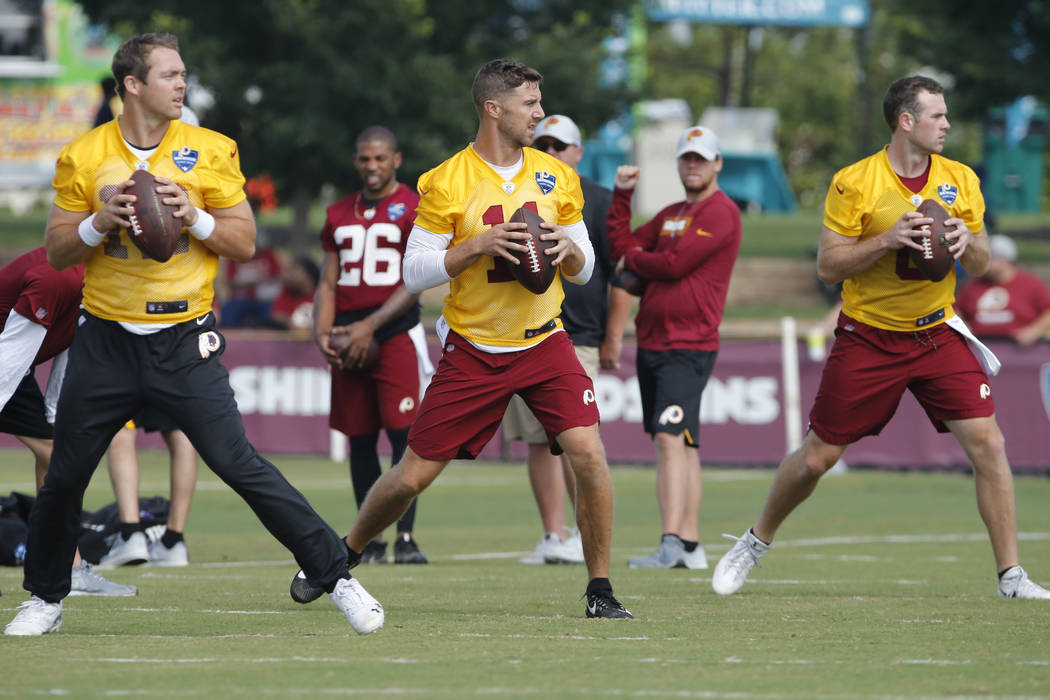 Washington Redskins quarterback Colt McCoy, left, Alex Smith, and Kevin Hogan, right, run drills during the morning session of NFL football training camp in Richmond, Va., Friday, July 27, 2018. ( ...