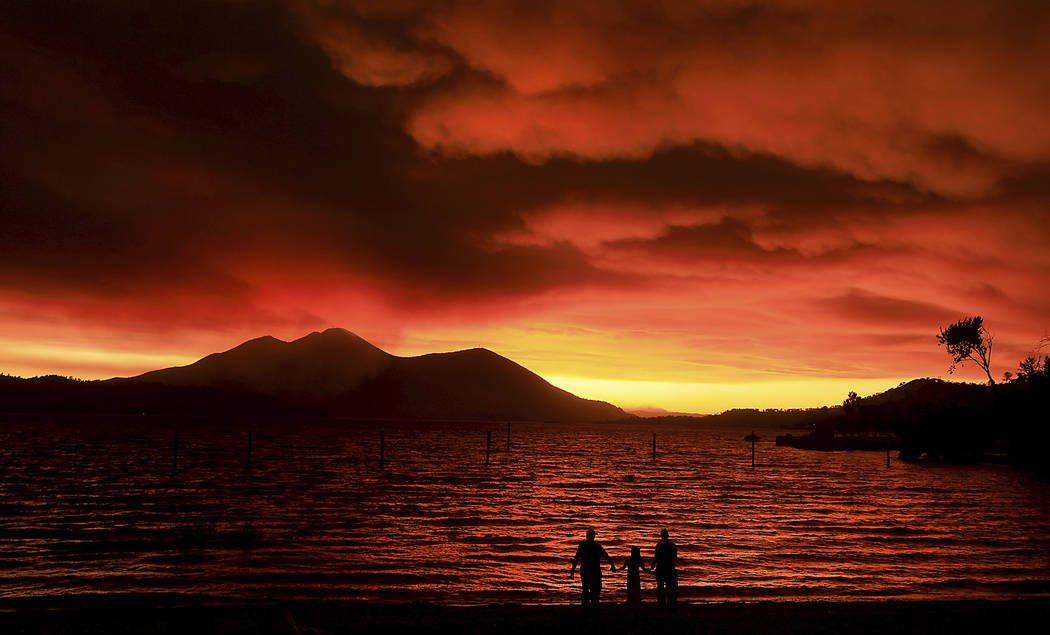 Evacuees from Lucerne, from left, Ken Bennett with Ember Reynolds, 8, and Lisa Reynolds watch the sunset as smoke from the Ranch Fire rises into the sky at Austin Park Beach in California's Clearl ...