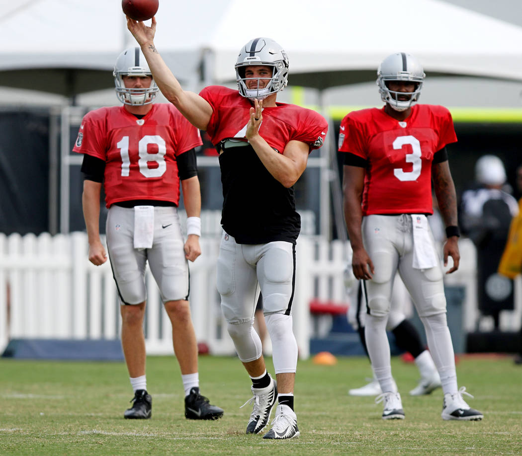 Oakland Raiders quarterback Derek Carr (4) throws the football as quarterbacks Connor Cook (18) and EJ Manuel (3) wait for their turn at the team's NFL training camp in Napa, Calif., Wednesday, Au ...