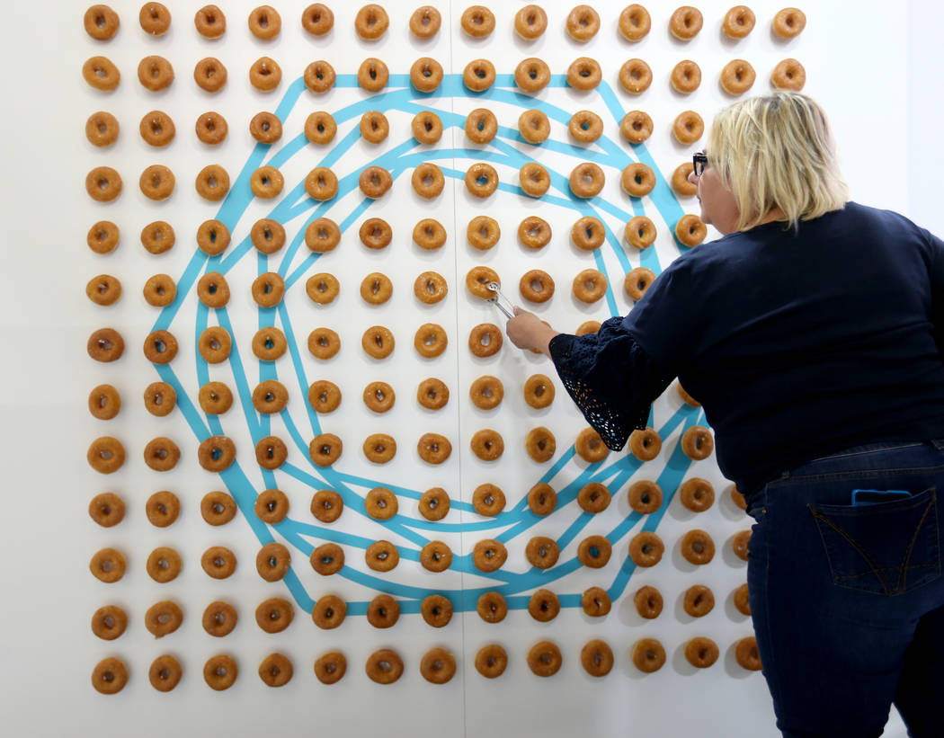 Maria Nardi of San Francisco reloads the donut wall in the Tenable booth at Black Hat USA cybersecurity conference at Mandalay Bay in Las Vegas Wednesday, Aug. 8, 2018. The company used the holes ...