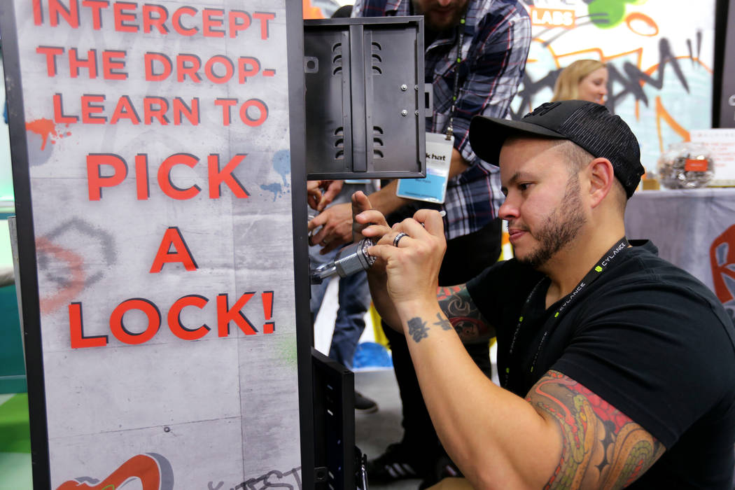 Joel Thomassino of Nashville tries to pick a lock to win a prize at the Coalfire Labs booth at Black Hat USA cybersecurity conference at Mandalay Bay in Las Vegas Wednesday, Aug. 8, 2018. K.M. Can ...