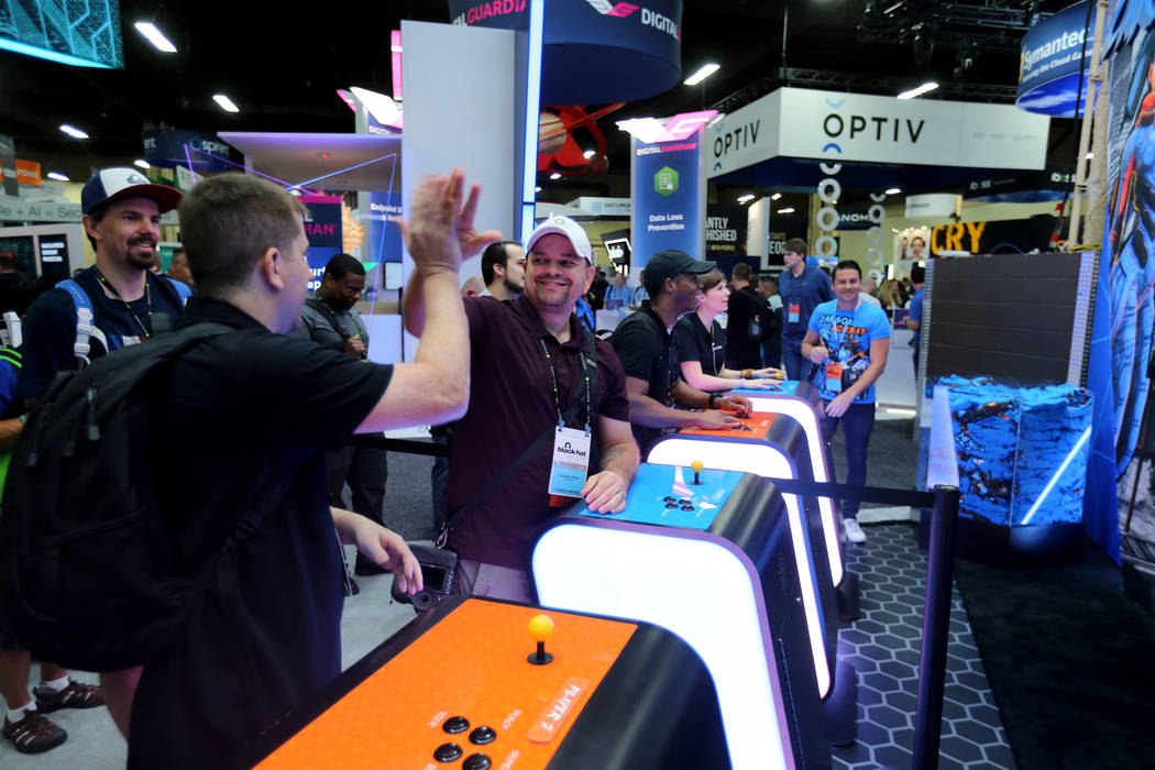 Jason Miller, left, and Donald Xavier of San Antonio, Texas play a video game at the Carbon Black booth at Black Hat USA cybersecurity conference at Mandalay Bay in Las Vegas Wednesday, Aug. 8, 20 ...