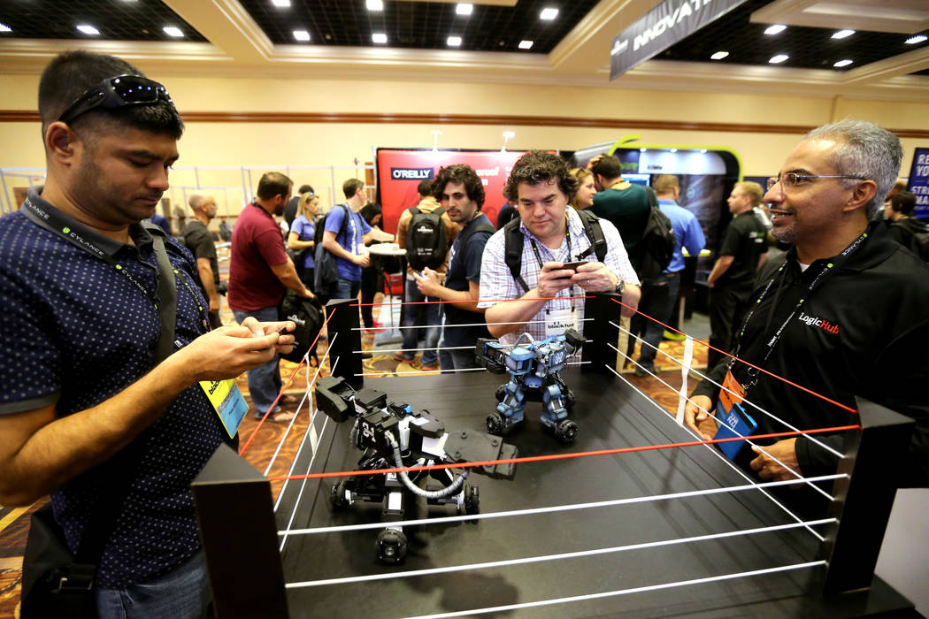 Padat Shrestha of Dallas, left, and Ricky Hohler of Overland Park, Kansas fight robots with the help of Normazd Romer of Mountain View, Calif., right, in the LogicHub booth at Black Hat USA cybers ...