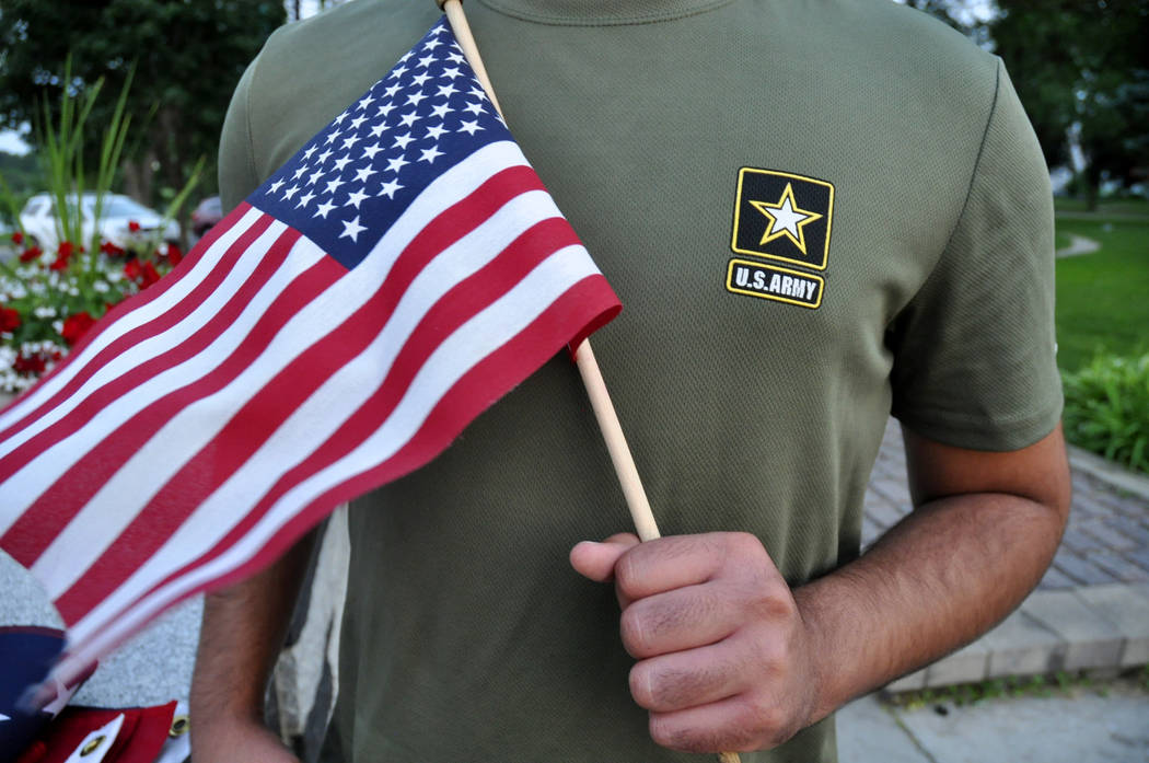 A Pakistani recruit, 22, who was recently discharged from the U.S. Army, holds an American flag, July 3, 2018. The U.S. Army has stopped discharging immigrant recruits who enlisted seeking a path ...
