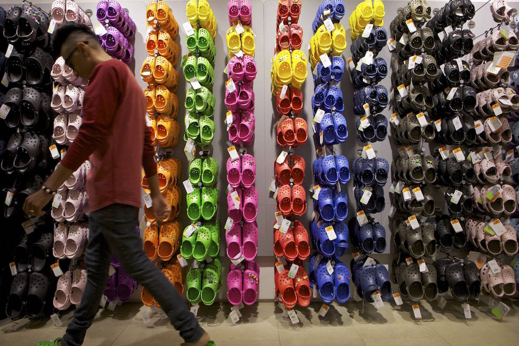 Summett Kumar, a Crocs ambassador, works at Crocs store inside the Beverly Center shopping mall in Los Angeles. (AP Photo/Damian Dovarganes, File)