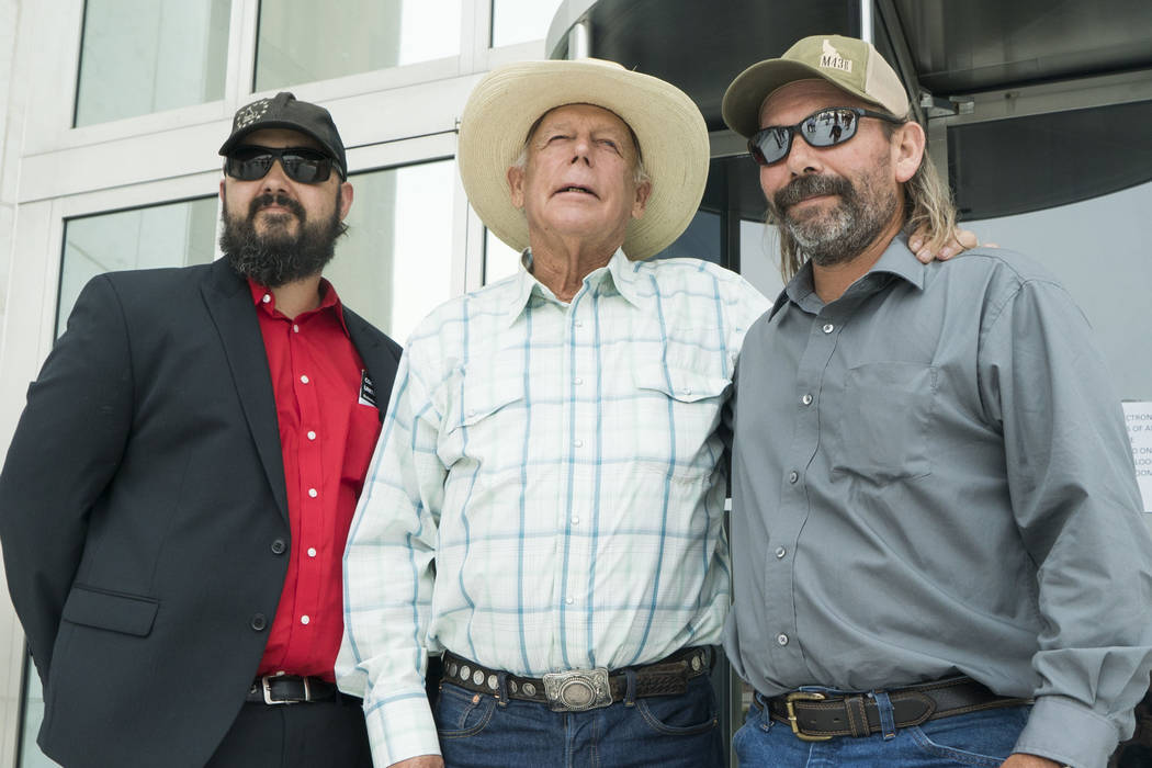 From left, Eric Parker, Cliven Bundy and Scott Drexler pose in front of the Lloyd George U.S. Courthouse after Drexler's court hearing in Las Vegas on Thursday, Aug. 9, 2018. U.S. District Judge G ...