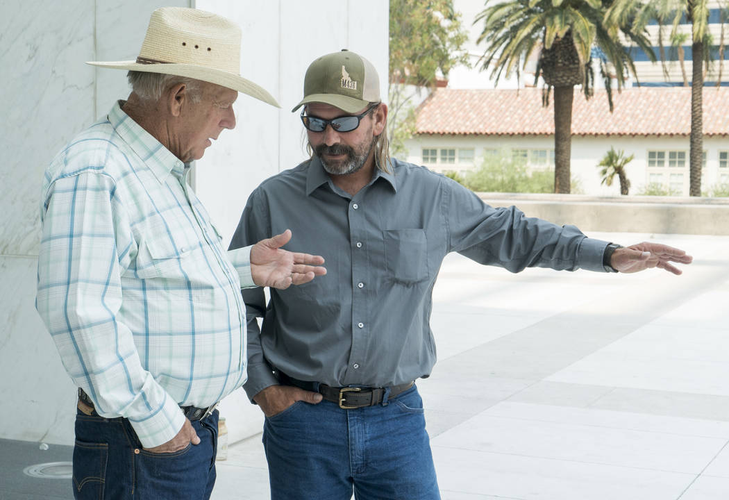 Rancher Cliven Bundy, left, talks to Scott Drexler outside the Lloyd George U.S. Courthouse in Las Vegas on Thursday, Aug. 9, 2018. U.S. District Judge Gloria Navarro decided that Drexler will not ...