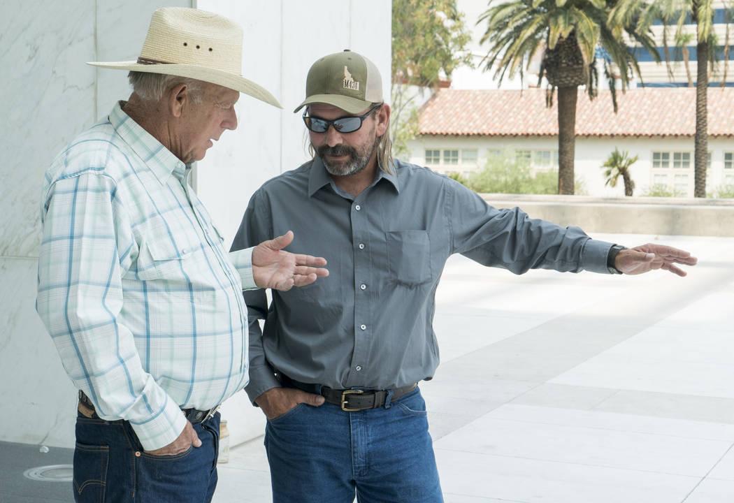 Rancher Cliven Bundy, left, talks to Scott Drexler outside the Lloyd George U.S. Courthouse in Las Vegas on Thursday, Aug. 9, 2018. U.S. District Judge Gloria Navarro decided that Drexler will not ...