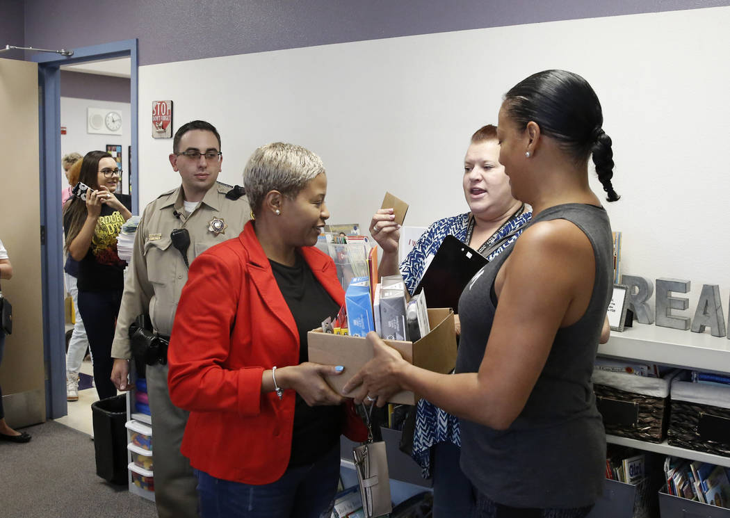 Downtown Container Park employee Cardiss Chung, left, delivers school supplies to first grade teacher Foster Patillo at Sunrise Acres Elementary School as Las Vegas police officer Cody Gill, left, ...