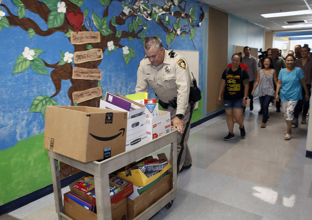 Las Vegas police officer Jay Hanson and Downtown Container Park employees deliver school supplies to Sunrise Acres Elementary School teachers on Thursday, Aug. 9, 2018, in Las Vegas. Bizuayehu Tes ...
