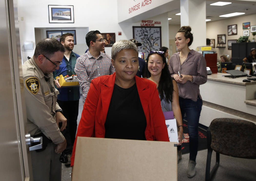 Downtown Container Park employees, including Cardiss Chung, front, deliver school supplies to Sunrise Acres Elementary School teachers as Las Vegas police officer Cody Gill, left, looks on Thursda ...