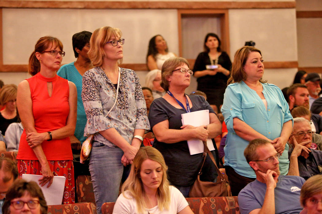Support staff stand while listening to a speaker at a Clark County School District board meeting at the Clark County Government Center in Las Vegas, Thursday, Aug. 9, 2018. The district's roughly ...
