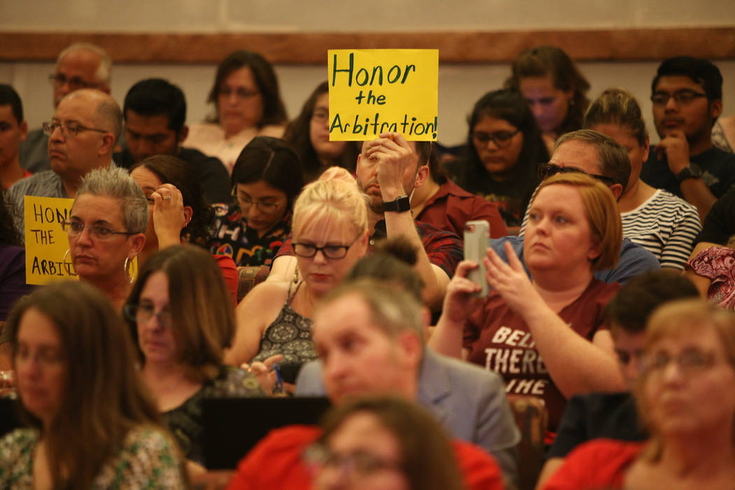 """A person holds a sign saying """"honor the arbitration"""" at a Clark County School District board meeting at the Clark County Government Center in Las Vegas, Thursday, Aug. 9, 2018. The distr ..."""