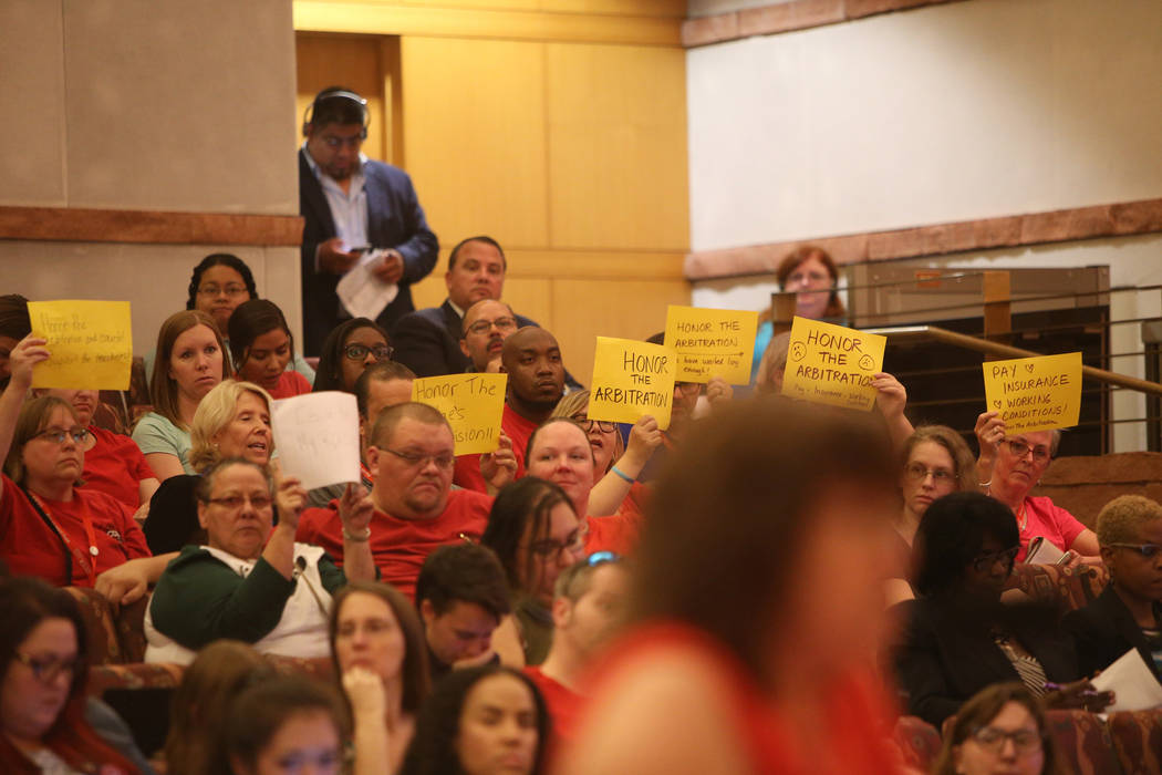 CCSD employees hold signs in protest as they listen to a speaker at a Clark County School District board meeting at the Clark County Government Center in Las Vegas, Thursday, Aug. 9, 2018. The dis ...
