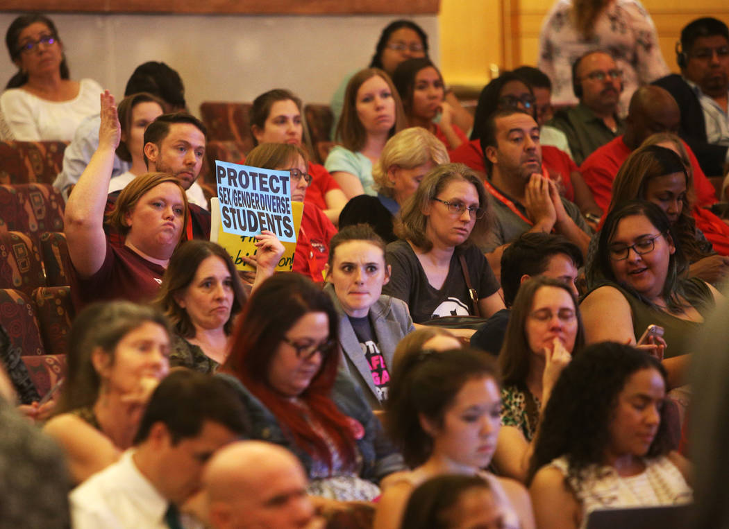 """A person holds a sign saying """"protect sex gender diverse students"""" at a Clark County School District board meeting at the Clark County Government Center in Las Vegas, Thursday, Aug. 9, 2 ..."""