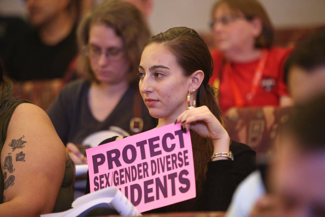 """Caity Gwin holds a sign saying """"protect sex gender diverse students"""" at a Clark County School District board meeting at the Clark County Government Center in Las Vegas, Thursday, Aug. 9, 2018. The ..."""