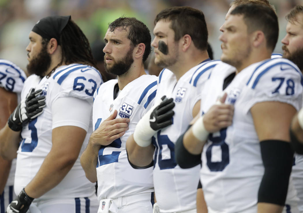 Indianapolis Colts players, including quarterback Andrew Luck, second from left, stand during the singing of the national anthem before an NFL football preseason game against the Seattle Seahawks, ...