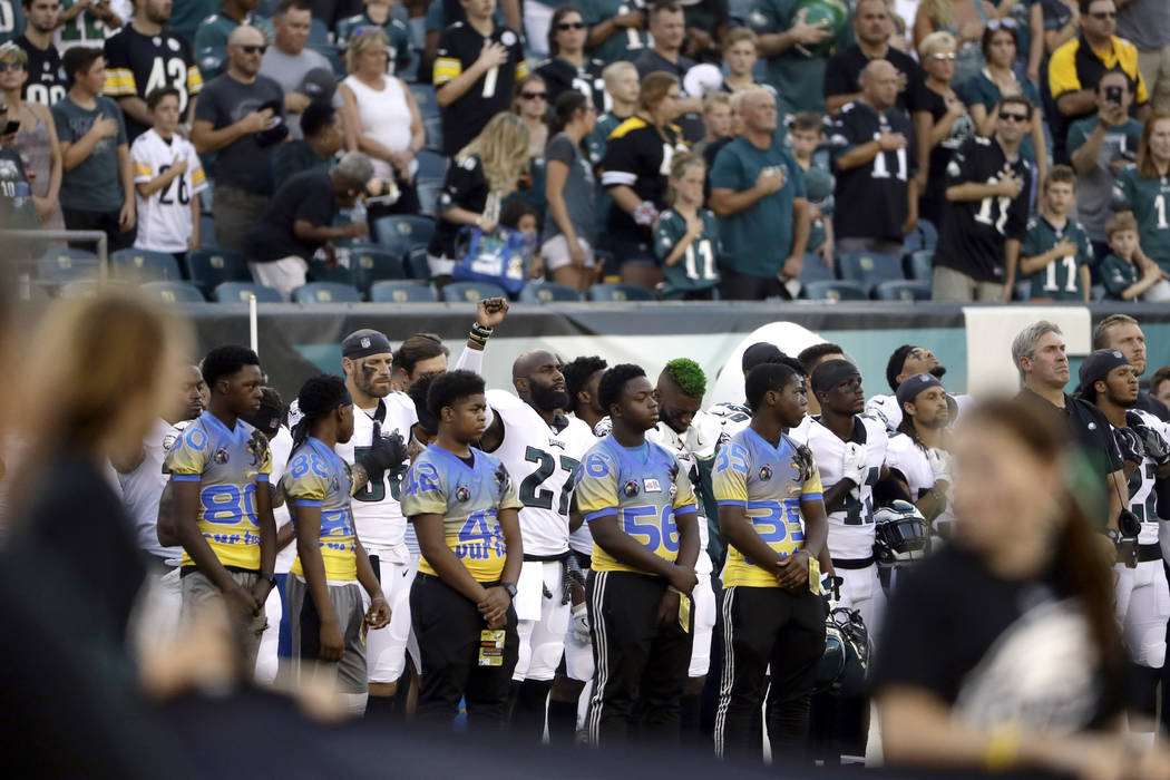 Philadelphia Eagles' Malcolm Jenkins, center left, raises his fist during the national anthem before the team's preseason NFL football game against the Pittsburgh Steelers, Thursday, Aug. 9, 2018, ...
