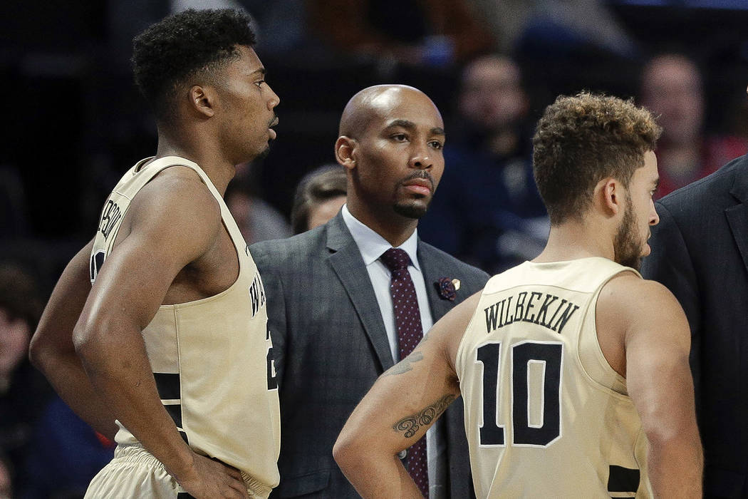 This photo from Nov. 28, 2017, shows Wake Forest assistant coach Jamill Jones, center, with the team during the second half of an NCAA college basketball game in Winston-Salem, N.C. Police say Jon ...