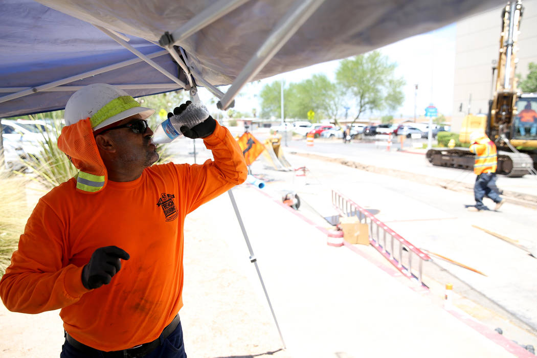 Ray Baez takes a water break under a shade structure as he and his crew work on Basic Road in Henderson. (K.M. Cannon/Las Vegas Review-Journal) @KMCannonPhoto
