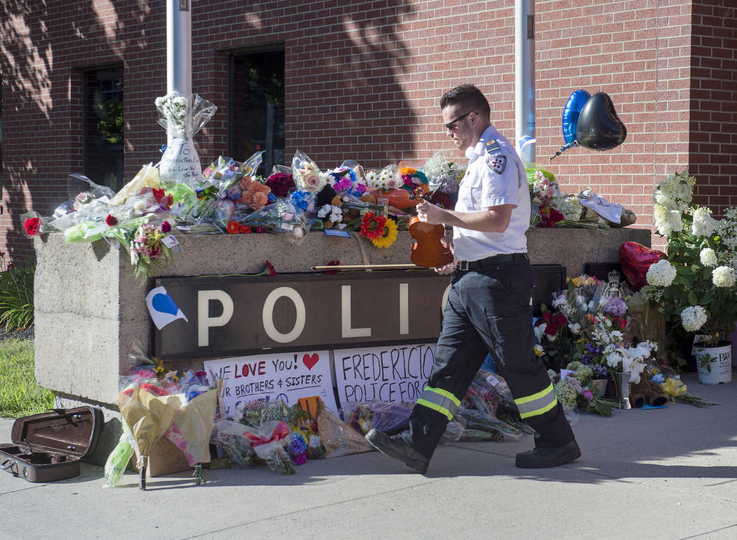 Paramedic Brian Fournier walks away after playing a hymn and placing a tribute at the police station in Fredericton, New Brunswick, Canada, on Friday, Aug. 10, 2018. (Andrew Vaughan/The Canadian P ...