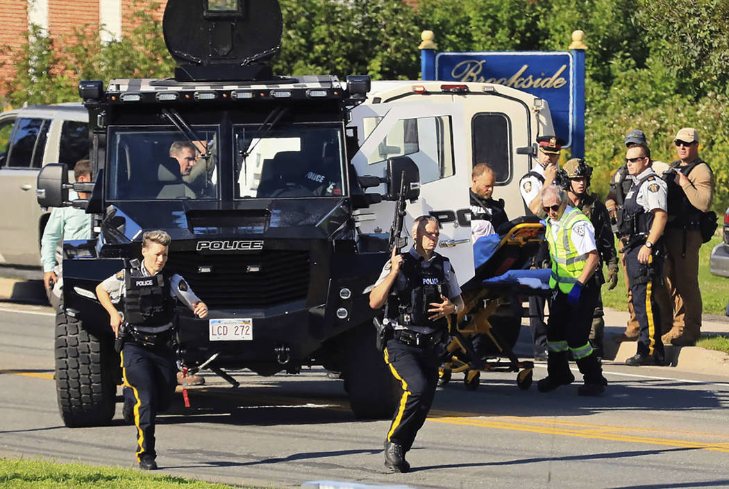 Police and RCMP officers survey the area of a shooting in Fredericton, New Brunswick, Canada on Friday, Aug. 10, 2018. (Keith Minchin/The Canadian Press via AP)
